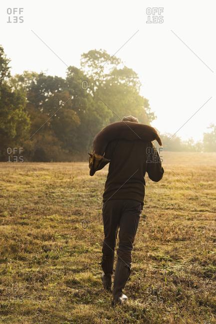 Hunter carrying dead deer
