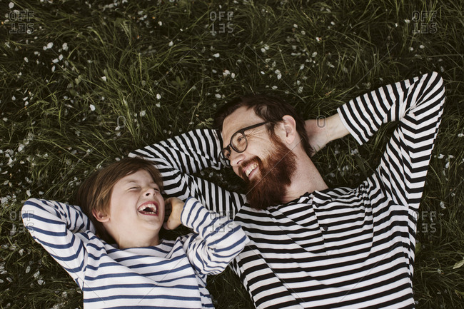 Father and son wearing similar stripped shirts lying on grass