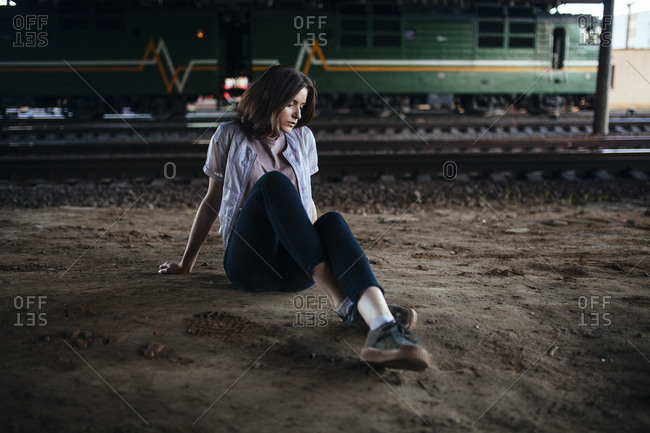 Woman sits on the ground near the railway