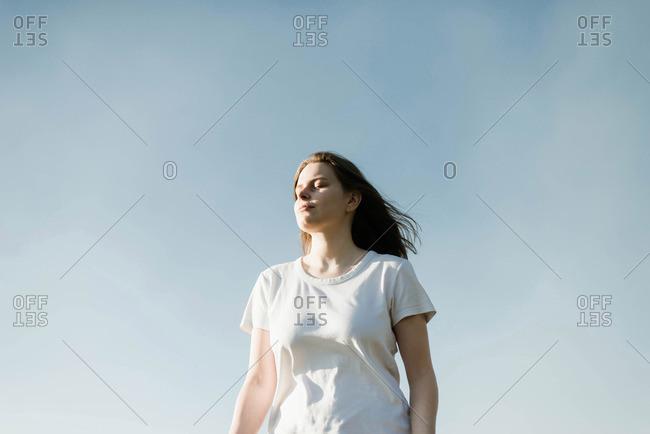 Dreamy portrait of a young brunette woman against the blue sky