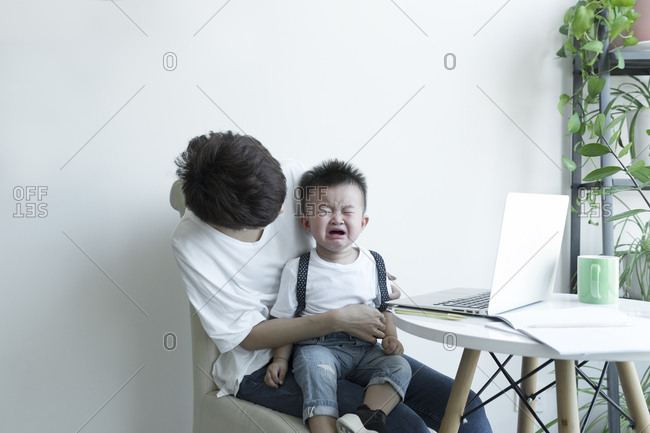 Vietnamese kid crying on mother's lap at home