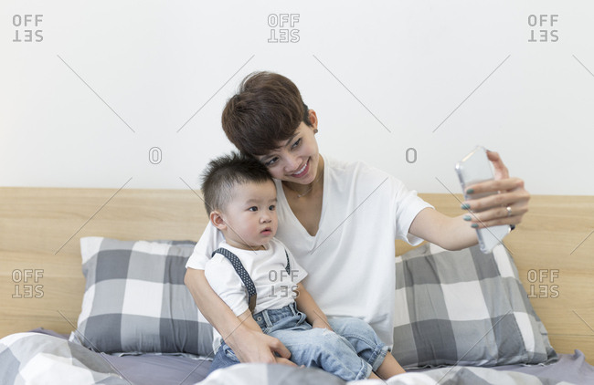 Asian woman and son taking selfie on the bed at home