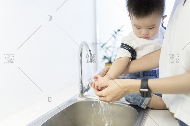 Asian mother and son washing hands together at home