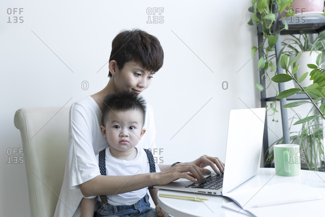 Asian mother using laptop with son on her lap looking at camera