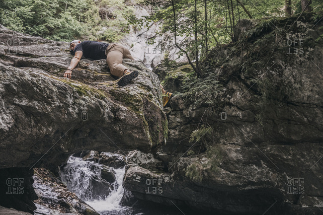 Man lies on rock during hike to waterfall in the Catskills, NY