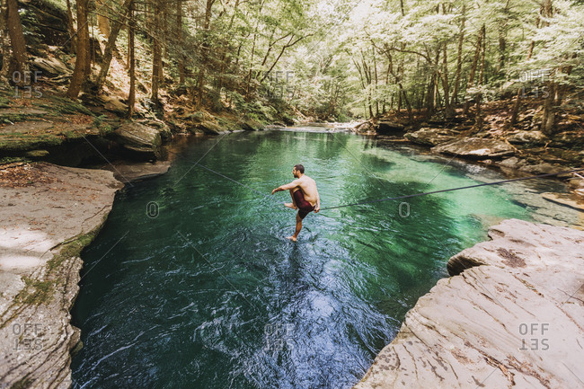 Man slacklines beautiful, blue spring in upstate New York, Catskills
