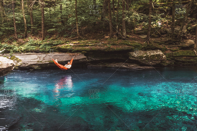 Man rests in hammock over beautiful, blue spring in upstate New York,
