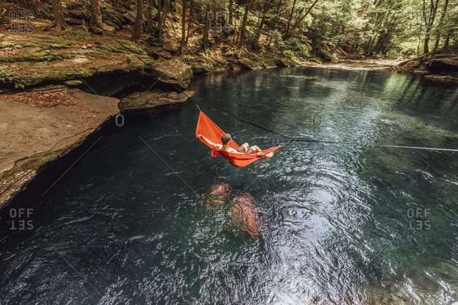 Man rests in hammock over beautiful, blue spring in upstate New York