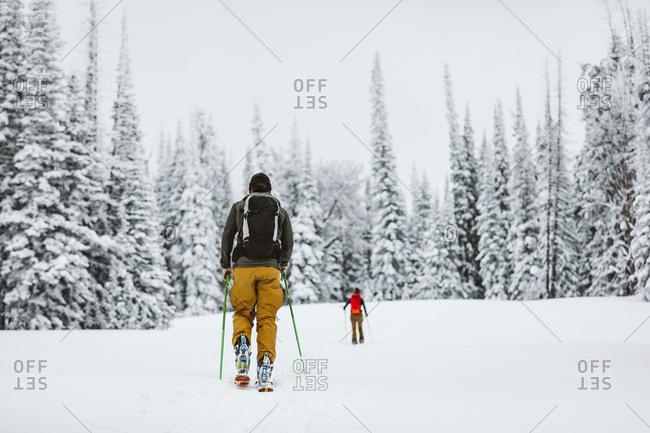 Two skiers head across a snowy field in Wyoming