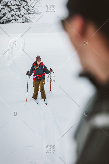 Young female skier heads down a hill as boyfriend watches