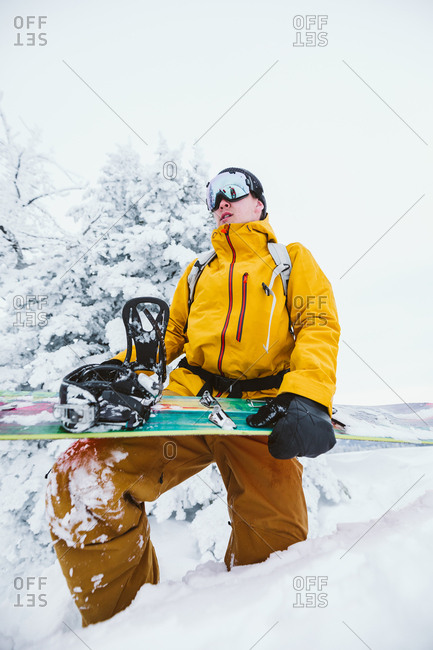 Young snowboarder gets ready to snowboard in a bright yellow jacket