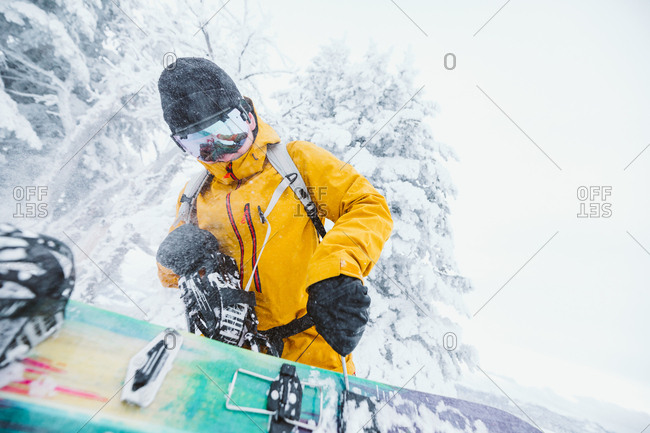 Snowboarder in yellow jacket fixes his snowboard on a blustery day