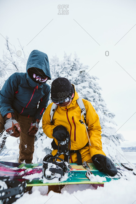 Two snowboarders get their boards ready