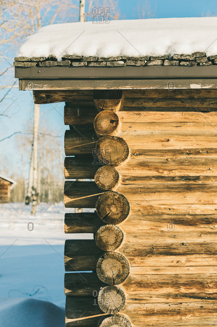 Snow covered old historic log cabin on a sunny day
