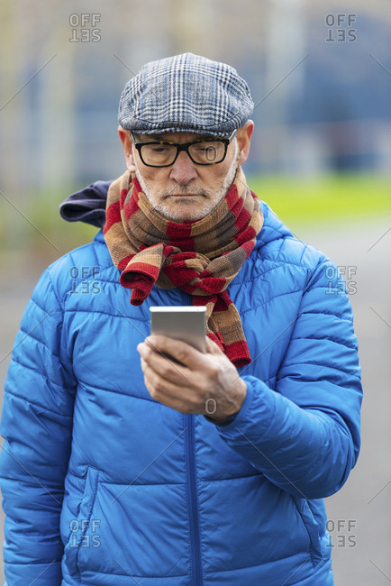 Confident senior man using smart phone, while standing outdoors