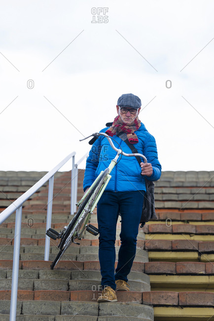 Senior man carrying bicycle while going down stairs against cloud sky