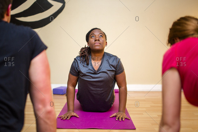 A woman arches back on an exercise mat with other yoga students
