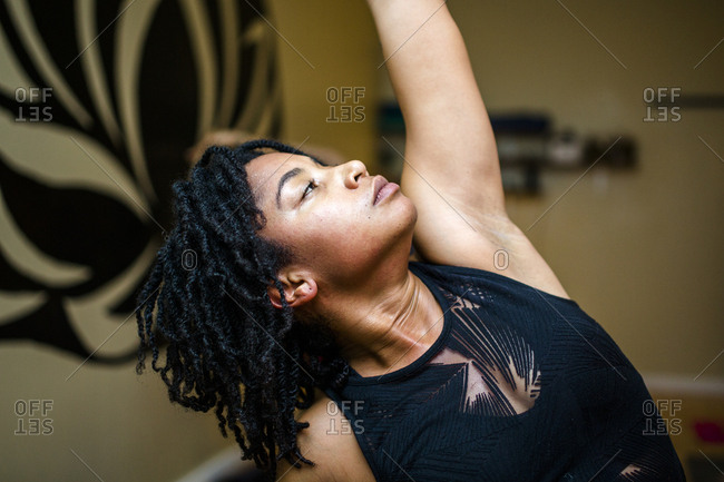 Side view of a beautiful woman, arm raised, relaxing in yoga position