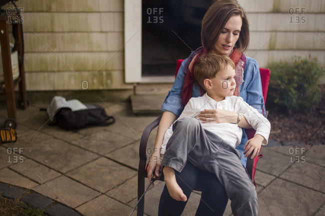 A mother sits outside with her small child in her lap
