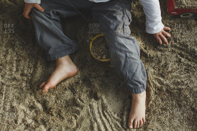 The bottom half of a small boy playing barefoot in a sandbox