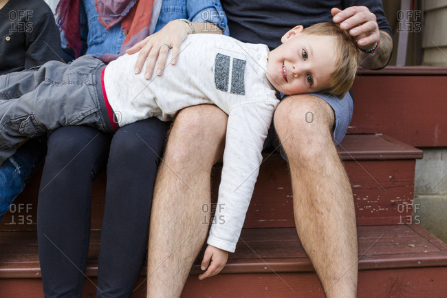 A small child rests on his parents laps outside