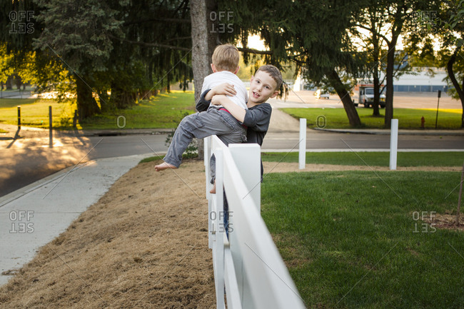 A boy helps his little brother get down from a fence
