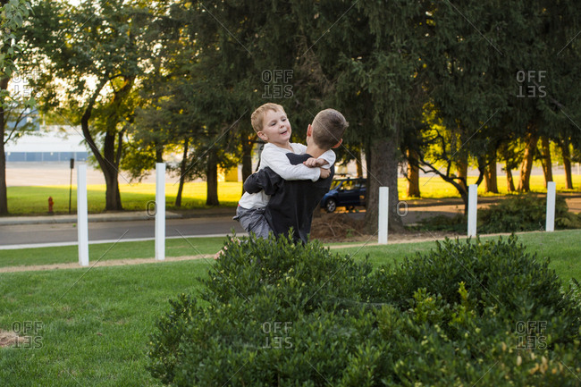 Two boys play together in front yard