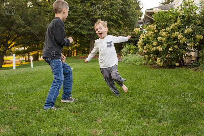 Two happy boys play together in front yard