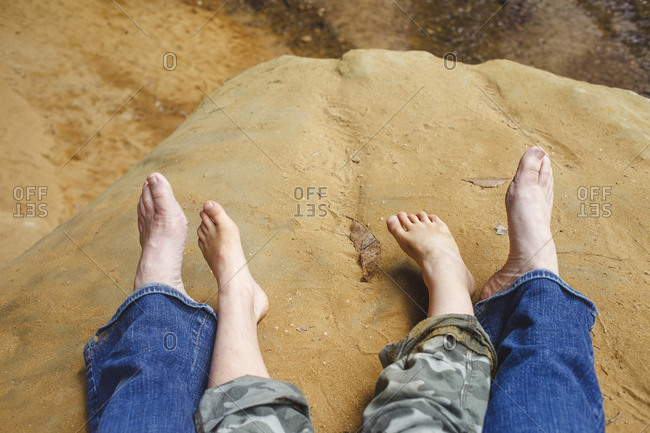 Lower section of a mother and child sitting barefoot on rock in gorge