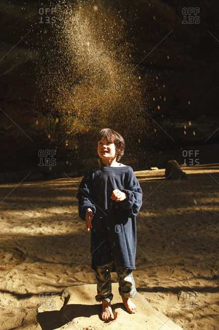 A small barefoot child throws golden sand into the air in sunlit gorge