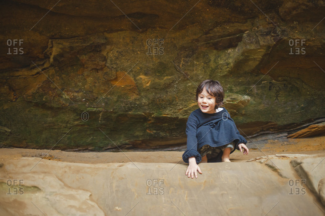 A small happy child crouches on a rocky ledge against sandstone cliff