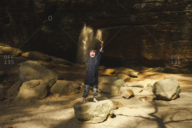 A small barefoot boy tosses golden sand in the air in a sunlit gorge