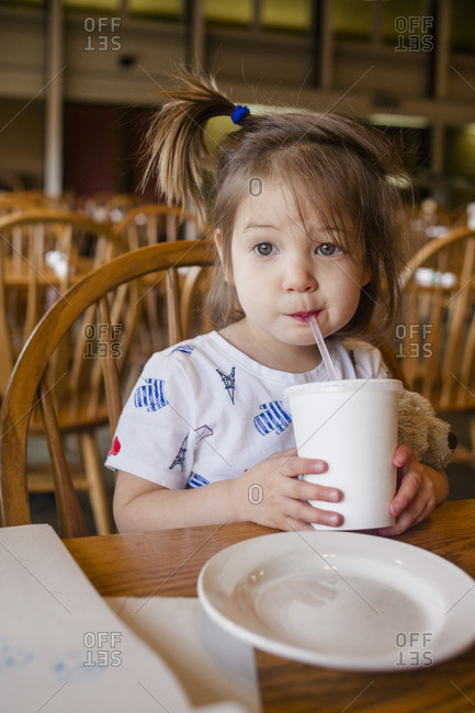 A cute little girl sips a drink out of a straw at a restaurant table
