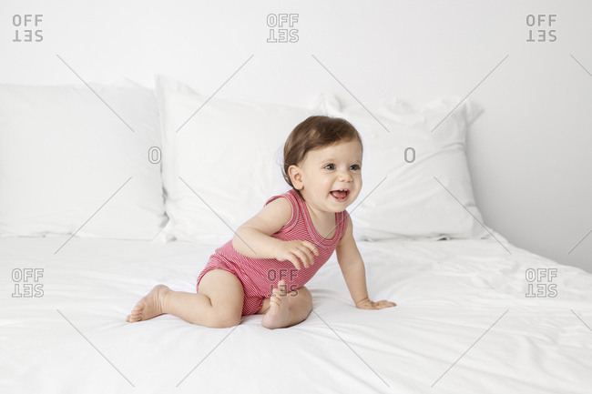 Laughing baby sitting on a white bed looking away