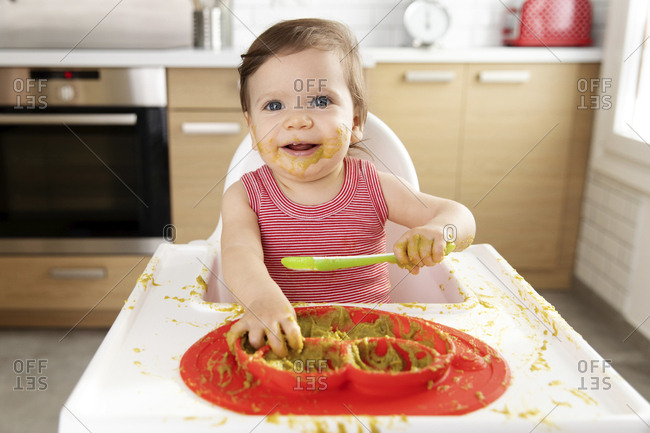 Messy baby in high chair eating pea puree with spoon