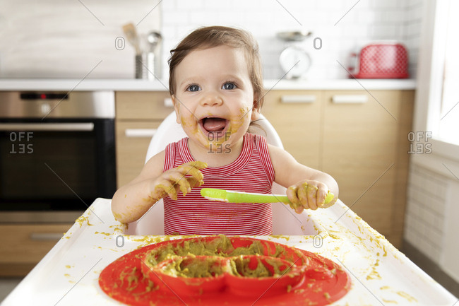 Happy baby in high chair making mess with pea puree