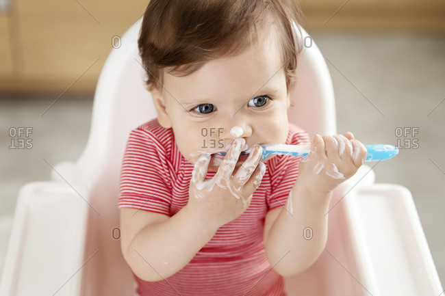 Baby with ginger hair eating yogurt with spoon