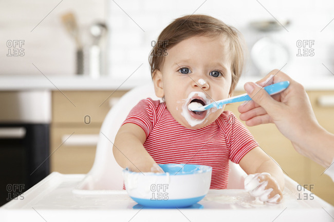 Baby sitting in high chair being fed with spoon