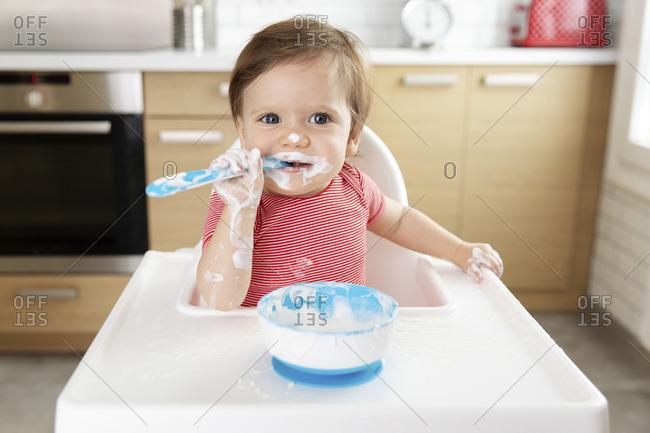 Baby in high chair eating yogurt by himself