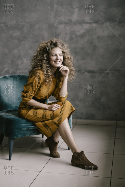 Young beautiful curly woman stands on the office in a retro dress