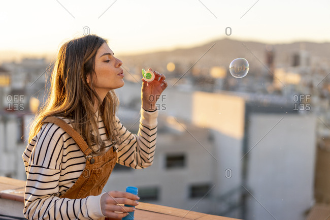 Young woman blowing soap bubbles on roof terrace in the evening