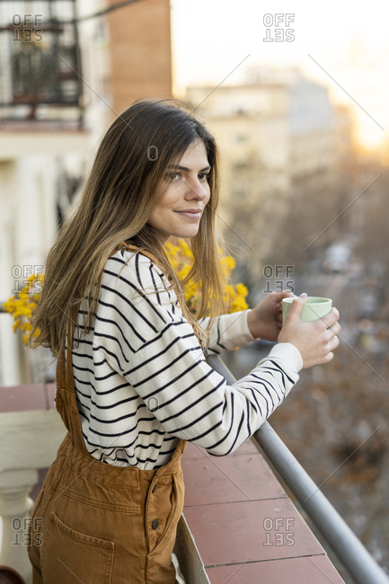Portrait of relaxed young woman standing on balcony with cup of coffee