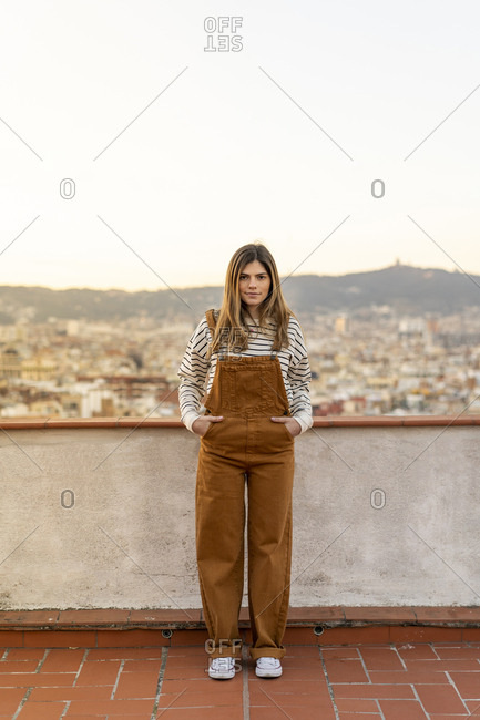 Portrait of young woman standing on roof terrace wearing brown dungarees