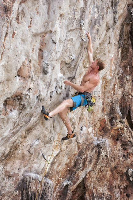 Thailand- Krabi- Lao Liang- barechested climber in rock wall