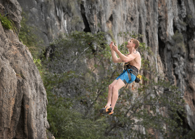 Thailand- Krabi- Lao Liang- barechested climber abseiling from rock wall