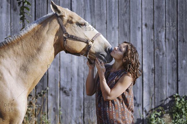 Pregnant woman stroking horse
