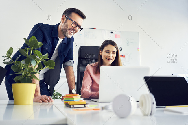 Two colleagues working together on laptop in office
