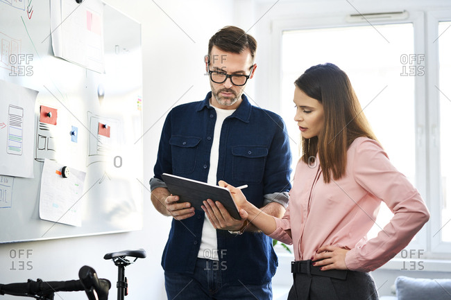 Two colleagues at whiteboard sharing tablet in office