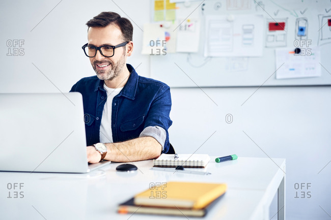 Casual businessman working on laptop at desk in office