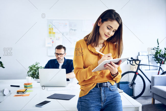 Businesswoman using tablet in office with colleague in background